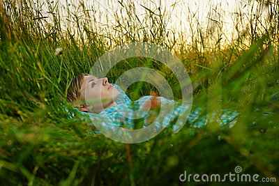 Young woman lie in the high grass