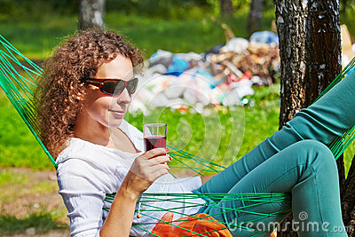Young woman lies in hammock with glass of beverage