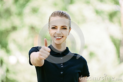 Young woman lifts thumb upwards