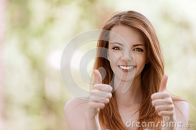 Young woman lifts thumbs upwards