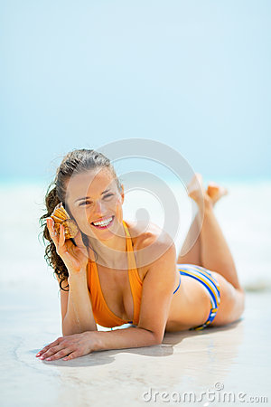 Free Young Woman Listening Sound Of Sea In Shell Royalty Free Stock Photo - 44216975