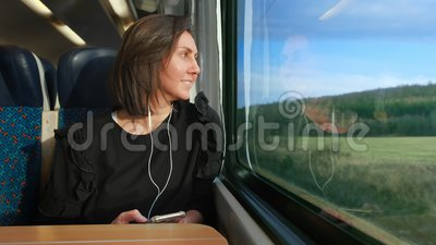 Woman listens to a player and goes on a train in Europe. A young woman listens to a player and goes on a train in Europe. A woman looks out the window at nature stock footage