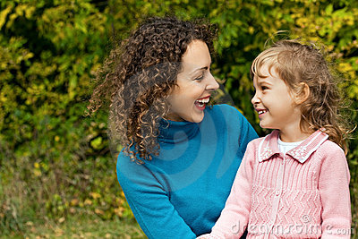 Young woman and little girl laugh in garden