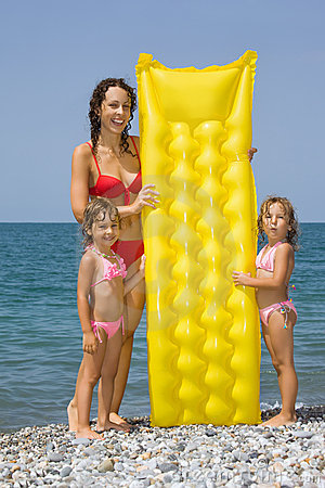 Young woman and little girls standing on beach