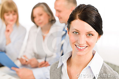 Young woman looking camera during meeting