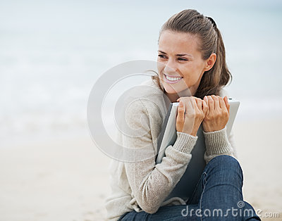 Young woman looking on copy space  while sitting on beach