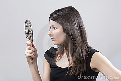 Young woman looking in a mirror