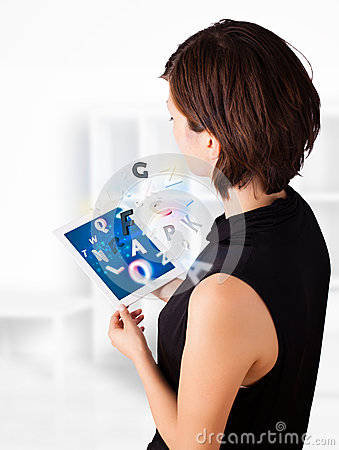 Young woman looking at modern tablet with alphabet