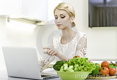 Young woman looking for a recipe on the laptop computer in the kitchen