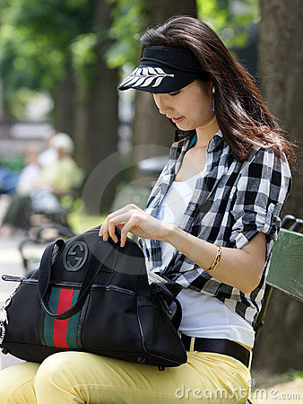 Young woman looking for something in your handbag