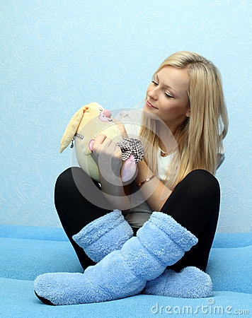 Young woman looking on toy rabbit