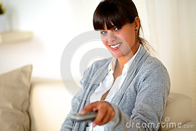 Young woman looking at you with tv remote