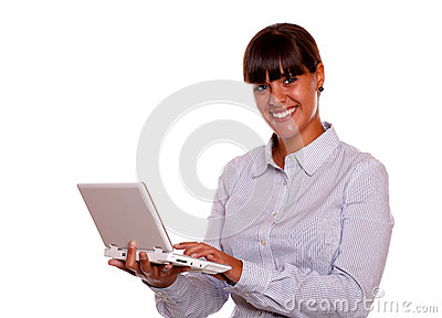 Young woman looking at you using laptop computer