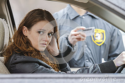 Young woman looks away after being pulled over by police