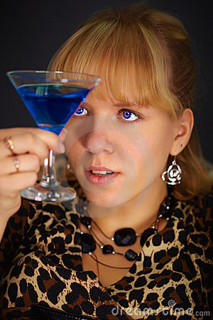 Young woman looks at glass with unusual cocktail
