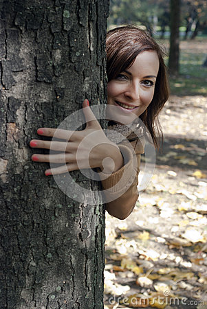 Young woman looks out from behind a tree