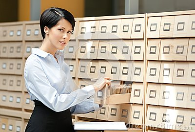 Young woman looks for something in card catalog