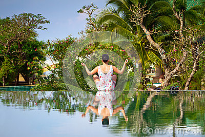 Young woman in lotus pose reflected in the water