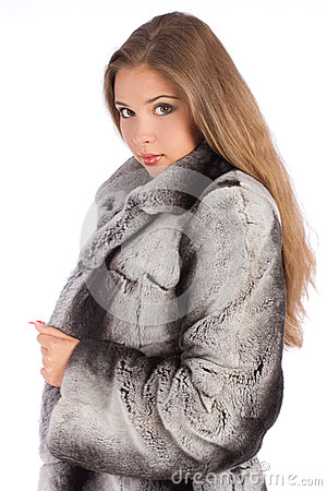 Young woman in luxury fur coat looking at camera