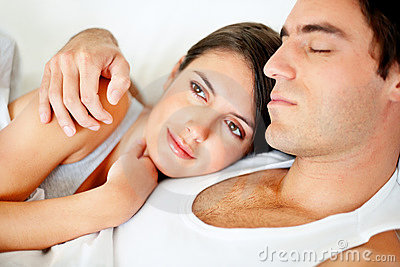 Young woman lying on bed with her husband