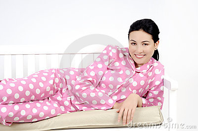 young woman lying in bedroom smiling