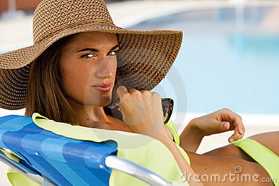 Young woman lying on deckchair by swimming-pool