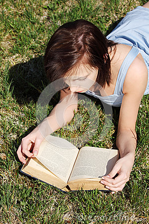 Young woman lying on grass, relaxing, reading book