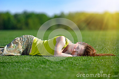Young woman lying on a green meadow