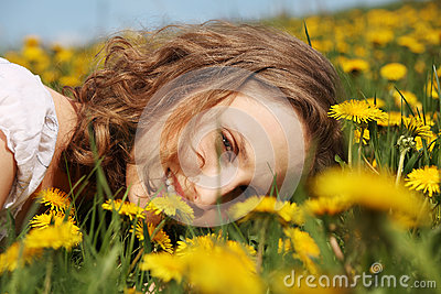 Young woman is lying on meadow.