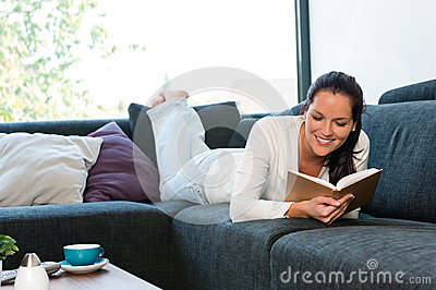Young woman lying reading book couch sofa