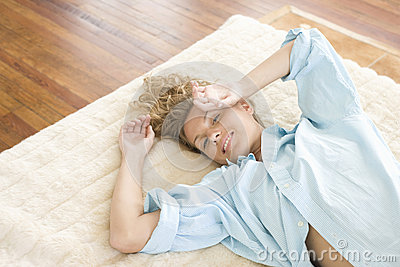 Young Woman Lying On Rug At Home