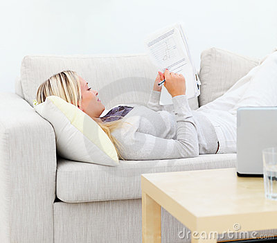 Young woman lying on sofa and writing documents