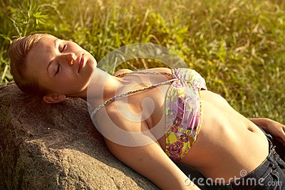 Young woman lying on the stone