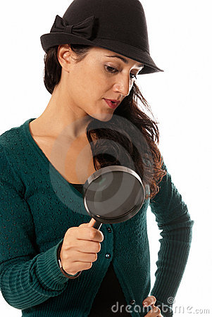 Young woman with magnifier glass and hat looking