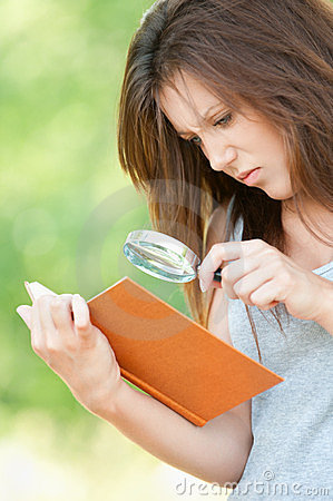 Young woman magnifier regards book