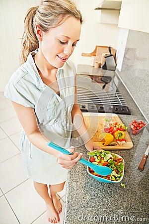 Young woman making salad