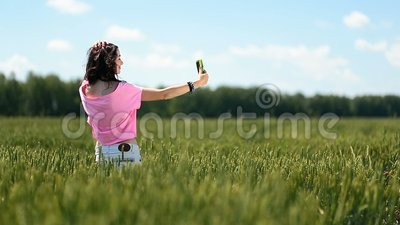Young woman making selfies in green wheat field stock footage