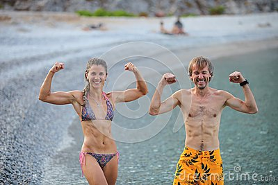 Young woman and man flexing their muscles jokingly