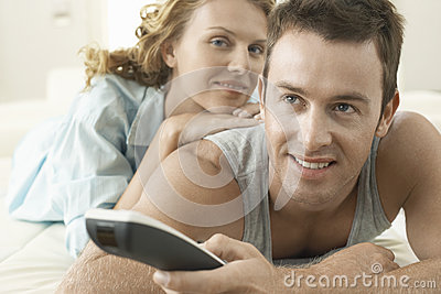 Young Woman With Man Holding Remote Control