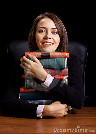 Young woman with many books at the desk