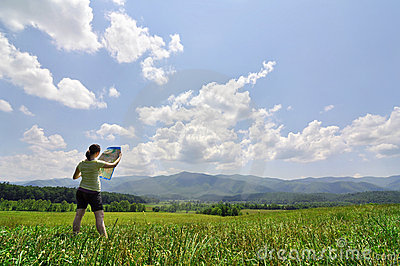 Young woman with map exploring a vast wilderness