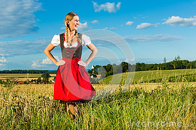 Young woman on meadow wearing dirndl
