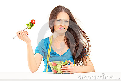 Young woman with measuring tape sitting and eating a salad