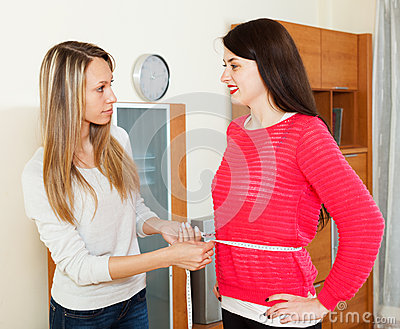 Young woman measuring  waist of smiling girlfriend