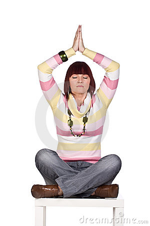 Young woman meditating cross-legged, isolated