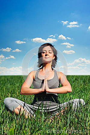 Young woman meditating on the field