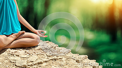Young woman meditating in the spring forest