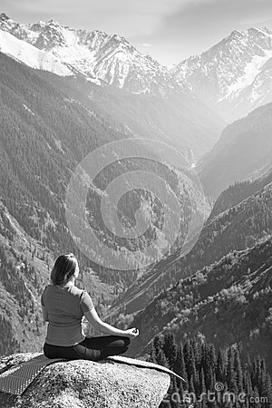 Young woman meditating on top of the mountain