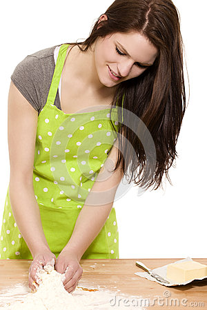 Young woman mixing dough