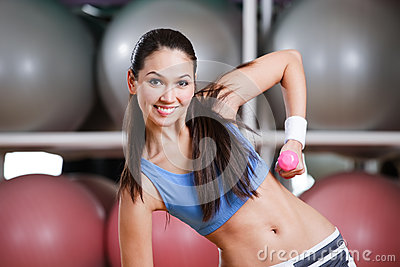 Young woman in motion with dumbbells